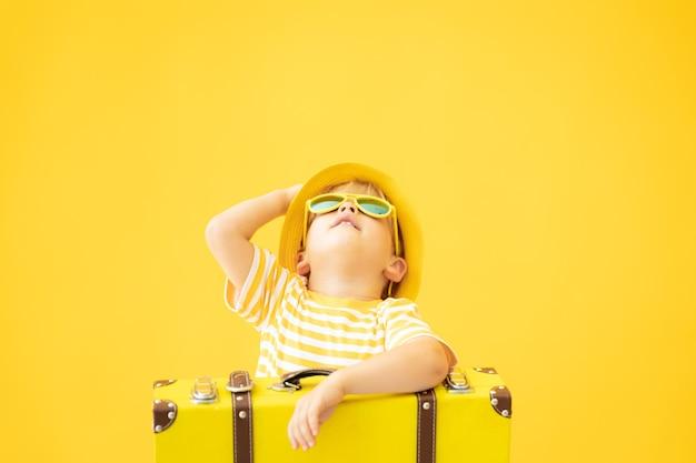 Retrato de niño feliz con maleta contra la pared amarilla en vacaciones de verano.