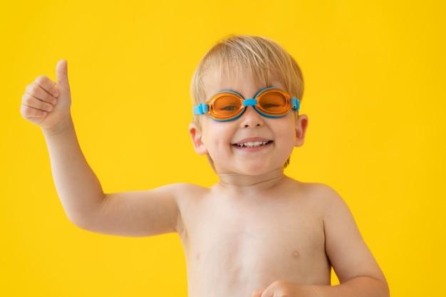Retrato de niño feliz mostrando los pulgares para arriba contra la pared amarilla en vacaciones de verano.