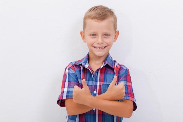 Retrato de niño feliz mostrando pulgares arriba gesto