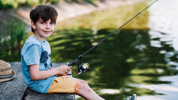 Retrato de un niño feliz pescando en el lago