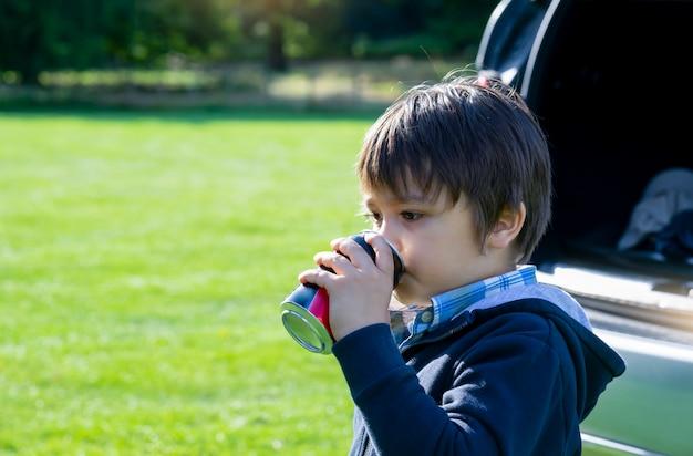 Retrato de niño feliz de pie junto a un coche bebiendo refrescos con una cara feliz, niño activo niño viajando en coche con sus padres durante las vacaciones escolares en verano, niño bebiendo bebidas gaseosas.