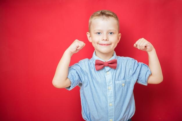 Retrato de un niño fuerte que muestra los músculos de sus brazos