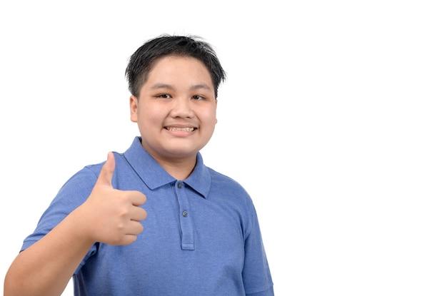 Retrato de niño gordo feliz asiático mostrando los pulgares para arriba gesto, aislado sobre fondo blanco.