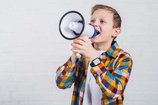 Retrato de un niño gritando a través del megáfono contra la pared de ladrillo blanco