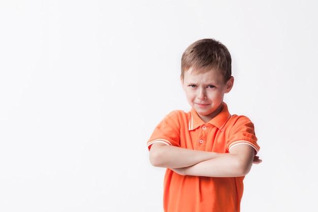 Retrato de niño inocente con el brazo cruzado contra la pared blanca