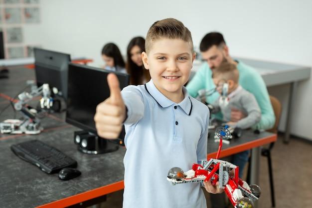 Retrato de un niño inteligente en una clase de robótica en la escuela sosteniendo un robot que ensambló