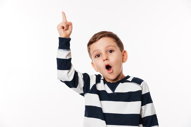 Retrato de un niño inteligente inteligente emocionado apuntando con el dedo hacia arriba