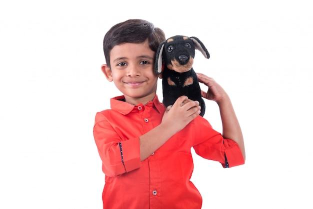 Retrato de niño jugando con su mascota de peluche en la pared blanca
