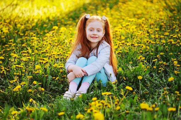 Retrato de un niño: una linda niña pelirroja en la superficie de un campo de dientes de león y vegetación.