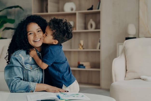 Retrato de niño lindo afroamericano en camiseta polo azul abrazando a la madre y besándola en la mejilla