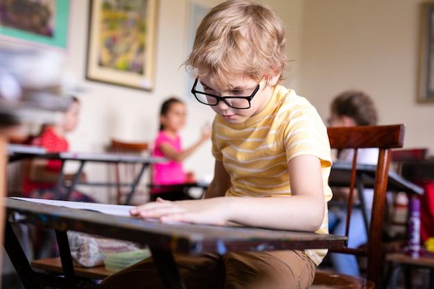 Retrato de niño lindo con bolígrafo y papel en el escritorio en el aula