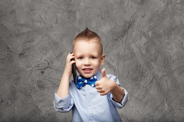 Retrato de un niño lindo en camisa azul y pajarita con teléfono móvil contra textura gris