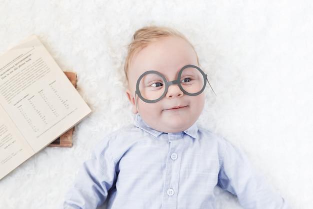 Retrato de un niño lindo en una camisa y gafas con libros acostado en la cama