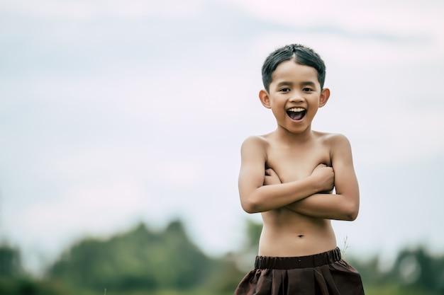 Retrato de niño lindo sin camisa en traje tradicional tailandés de pie y con los brazos cruzados sobre el pecho, ríe con timidez, espacio de copia