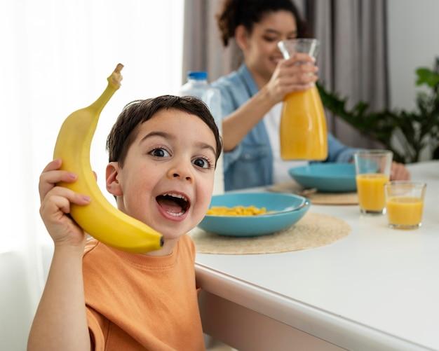 Retrato de niño lindo jugando con plátano en la mesa del desayuno