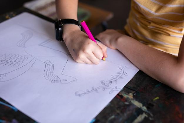 Retrato de niño lindo con lápiz de dibujo y papel en el escritorio en el aula.