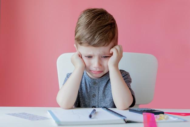 Retrato de niño lindo niño en casa haciendo la tarea. pequeño niño concentrado escribiendo con lápiz de colores, en el interior.