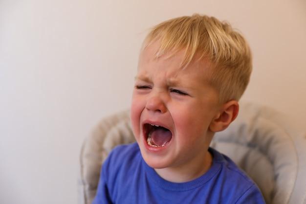 Retrato de un niño llorando con cabello rubio