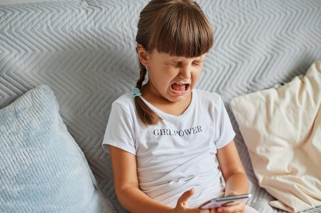 Retrato de niño llorando lindo molesto con cabello oscuro y coletas, sentado en el sofá con el teléfono celular en las manos, triste por perder nivel en su juego favorito, con camiseta blanca.