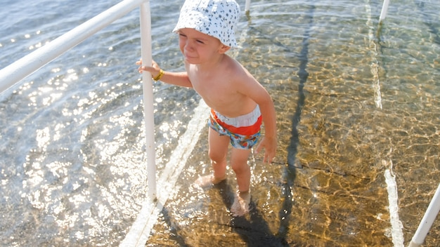 Retrato de niño llorando de pie en agua de mar fría.