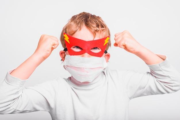 Retrato de niño con máscara de superhéroe con la boca cubierta con una máscara médica para protegerse