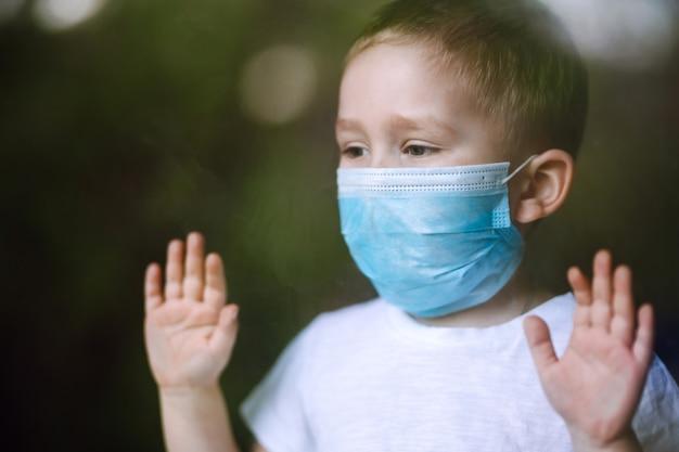 Retrato de niño con mascarilla médica mirando a la cámara en la ciudad