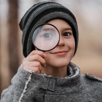 Retrato de niño mirando a través de una lupa