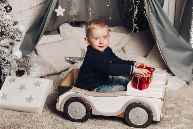 Retrato niño muestra cajas de navidad con regalos
