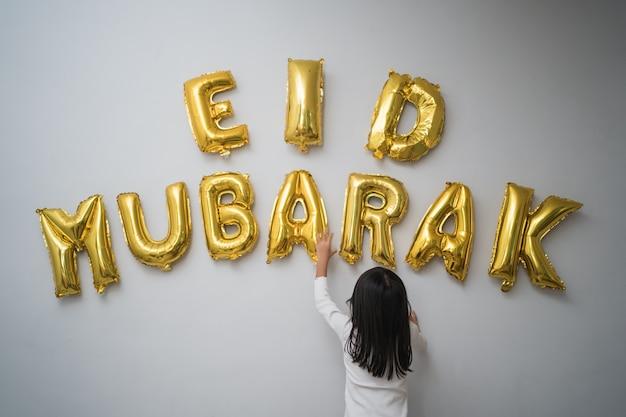 Retrato niño musulmán que adorna la letra de eid mubarak hecha de la decoración del globo contra la pared en casa