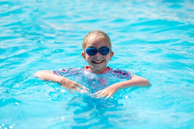 Retrato de un niño muy feliz en un traje de baño brillante y gafas azules, que está en la piscina al aire libre bajo el sol