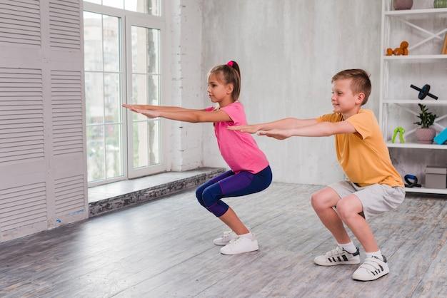 Retrato de un niño y una niña haciendo ejercicio en casa