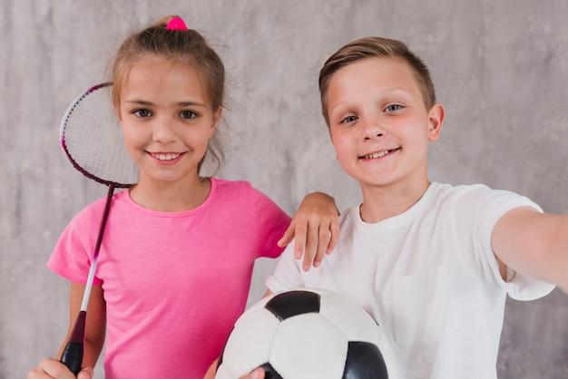 Retrato de un niño y una niña con raqueta y balón de fútbol frente a un muro de hormigón
