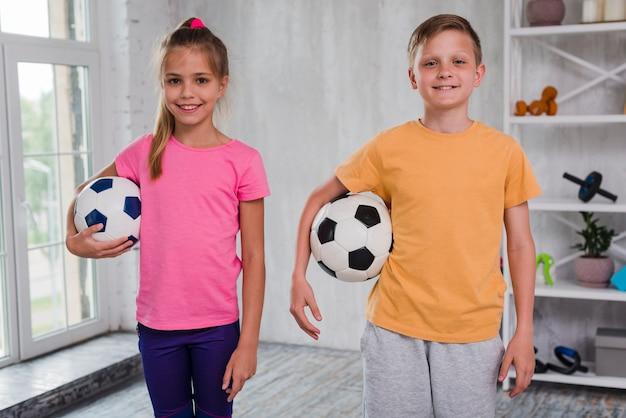 Retrato de un niño y una niña sonrientes que sostienen el balón de fútbol que mira la cámara
