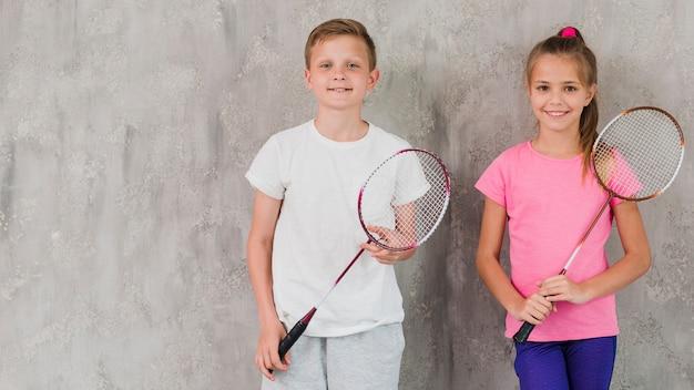 Retrato de un niño y una niña sonrientes sosteniendo la raqueta en las manos contra el muro de hormigón