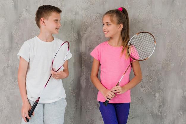 Retrato de un niño y una niña sosteniendo una raqueta en la mano de pie delante de un muro de hormigón