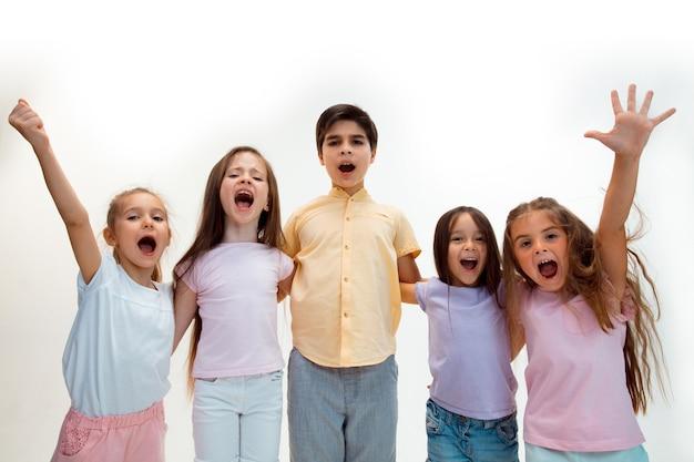 El retrato de niño y niñas felices lindos niños pequeños en ropa casual elegante mirando al frente contra la pared blanca del estudio
