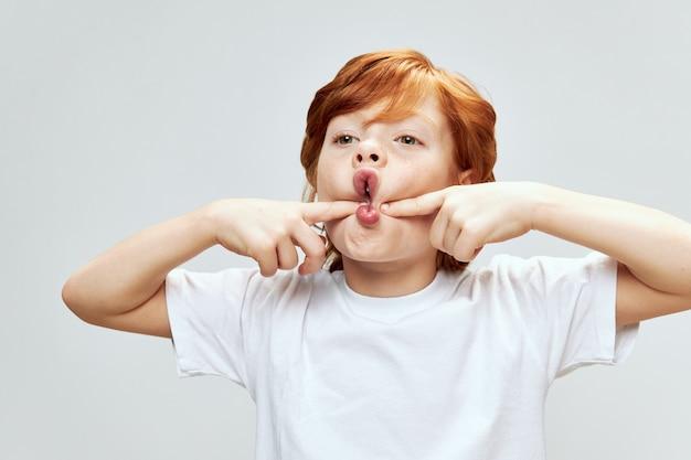 Retrato de niño pelirrojo cogidos de la mano en las mejillas con la boca abierta. vista recortada sobre un fondo gris