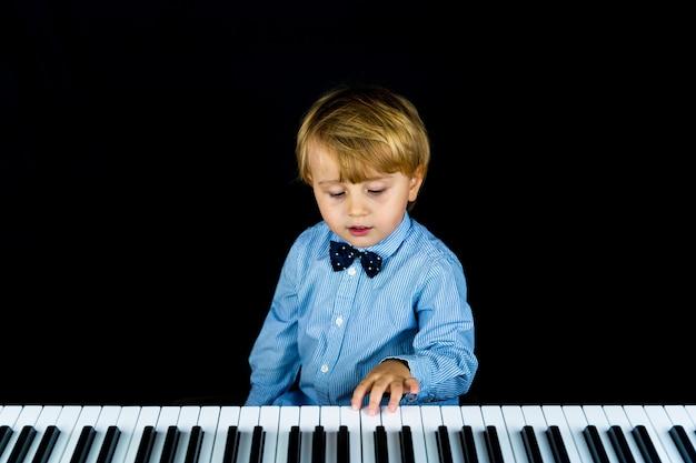 Retrato de un niño pequeño adorable con camisa elegante y pajarita de cerca.