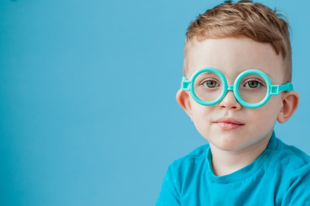 Retrato de un niño pequeño con gafas de juguete sobre fondo azul.