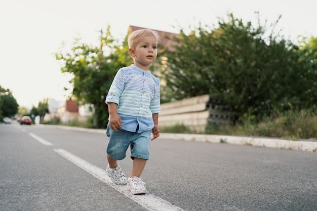 Retrato del niño pequeño lindo que camina en el camino en su vecindario