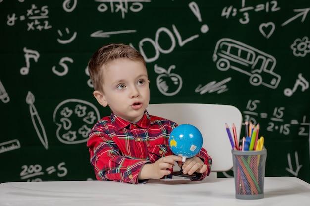 Retrato del niño pequeño lindo que sostiene en globo pequeño de las manos en fondo de la pizarra. listo para la escuela. de vuelta a la escuela.
