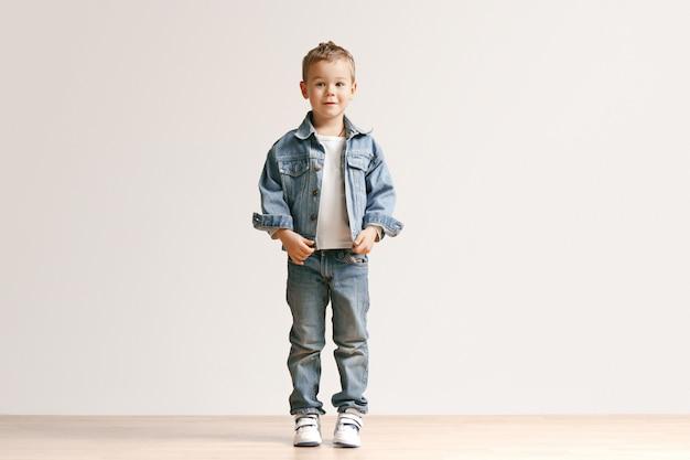 El retrato del niño pequeño lindo en ropa elegante de los vaqueros que mira la cámara contra la pared blanca del estudio.