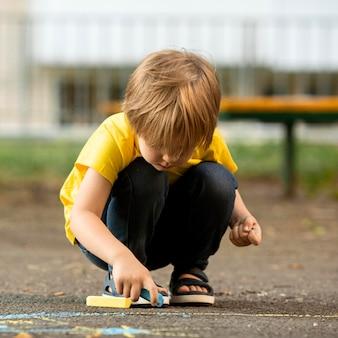 Retrato de niño pequeño en el parque de dibujo