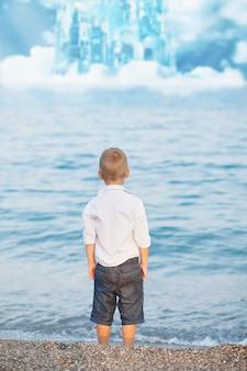 Retrato con niño pequeño de pie en la playa