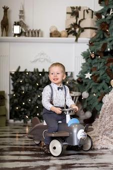 Retrato de un niño pequeño sentado en un avión de juguete vintage cerca de un árbol de navidad. decoraciones de navidad. el niño se regocija con su regalo de navidad. feliz navidad y próspero año nuevo