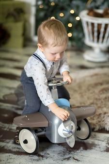 Retrato de un niño pequeño sentado en un avión de juguete vintage cerca de un árbol de navidad