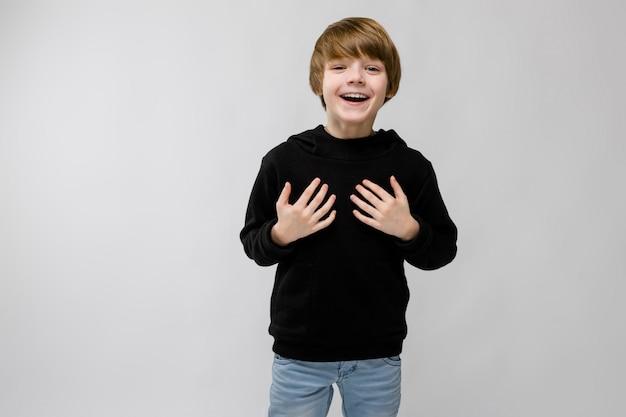 Retrato del niño pequeño smilling adorable que se coloca con las manos en su pecho en gris