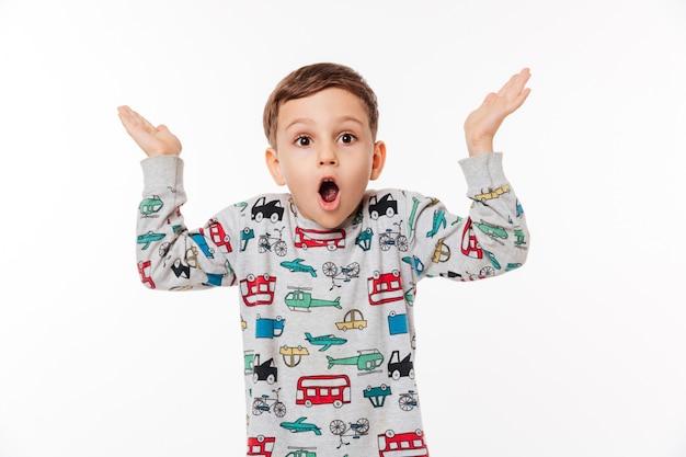 Retrato de un niño pequeño sorprendido de pie y encogiéndose de hombros