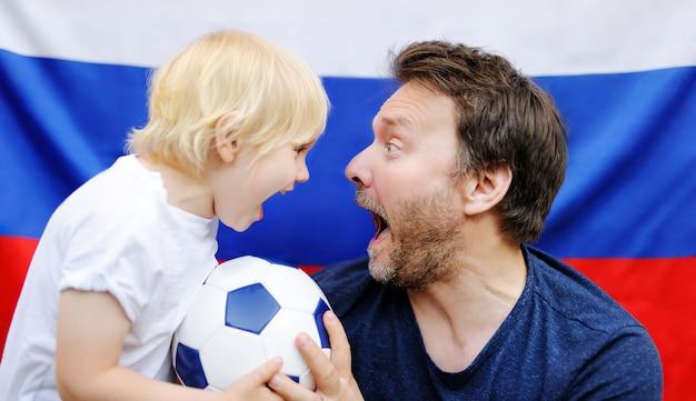 Retrato de niño pequeño y su padre de mediana edad con bandera rusa en el fondo