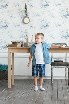 Retrato de un niño de pie cerca de la mesa en la sala de estar